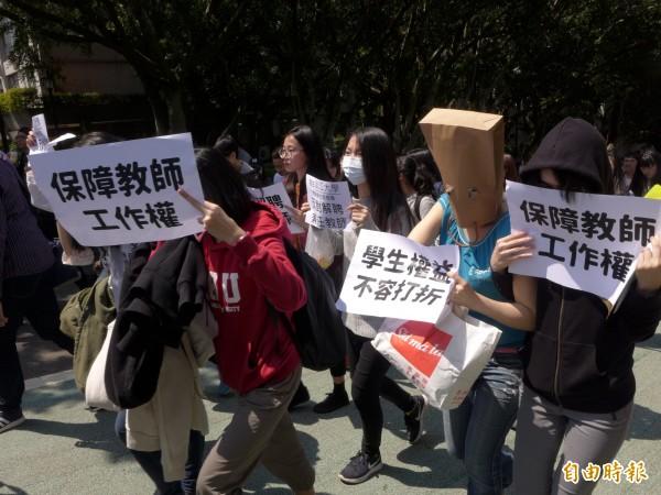 參與活動的學生手裡拿著寫有「保障教師工作權」、「學生權益不容打折」等訴求的海報。(記者李雅雯攝)