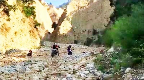 5輛越野機車沿著沖蝕溝中的卵石流往上騎。(警方提供)