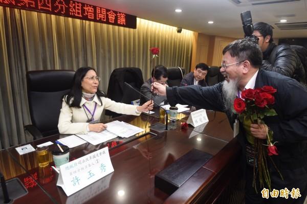 推動陪審制的台灣陪審團協會理事長張靜,今天在參加司法國是會議第四組公聽會前,向與會法官發送玫瑰。(記者叢昌瑾攝)