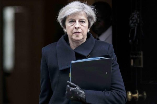 英國首相梅伊在22日國會恐攻發生時,在特勤保護下撤離。(路透)
