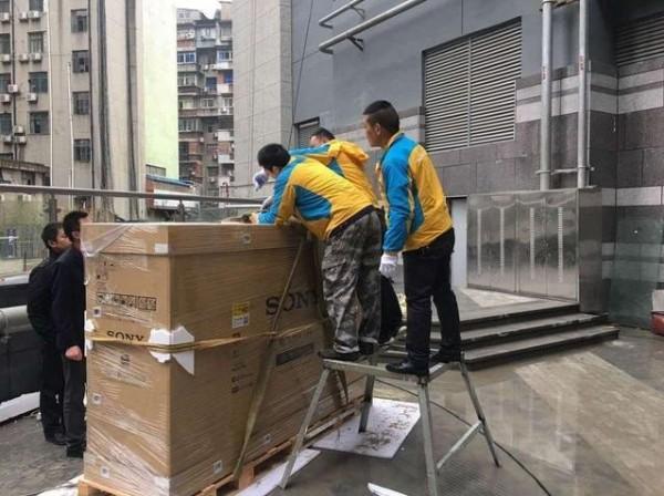 工作人員們正在固定200多公斤的大電視。(圖擷取自湖北日報網)