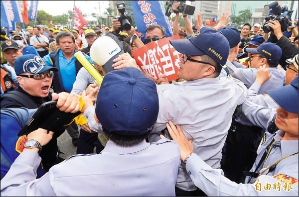 ▲「台灣警消聯盟」等反年金改革團體,昨串聯發起「遍地開花」遊行抗爭活動,圖為前往行政院的抗議群眾數度和員警爆發推擠衝突。(記者廖振輝攝)