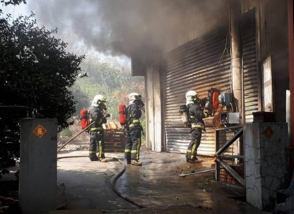 彰化市岸頭巷五金工廠今天下午傳出火災,消防員以切割器材破壞鐵捲門搶救。(記者湯世名翻攝)