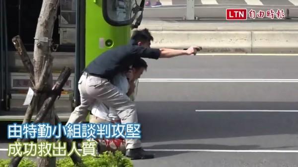 世大運防恐演習,其中一名歹徒持搶挾持一輛公車的乘客當人質,對話以台語演出,引起歧視台語的質疑。(記者蔡文居翻攝)