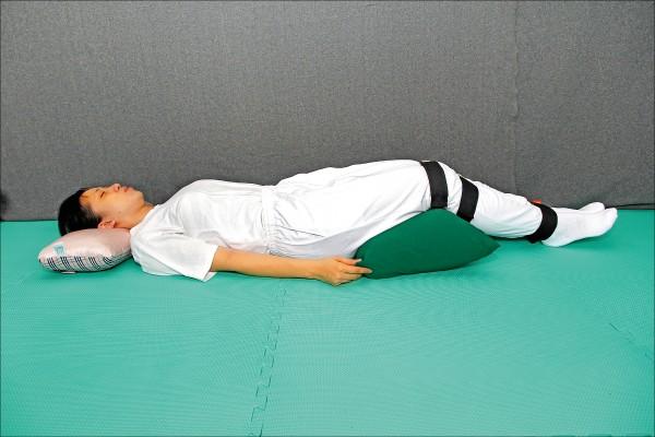 「QMAX復元枕」,透過特殊造型的枕頭與綁腿,讓民眾可以達到復健師徒手復健效果。(洪斯文提供)