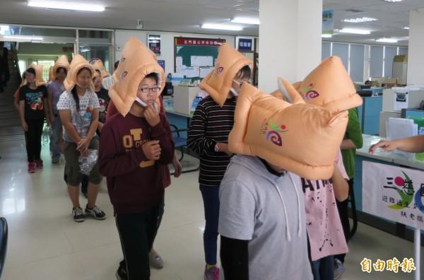 學生戴上防災頭套保護頭部,演練地震緊急避難。(記者楊金城攝)