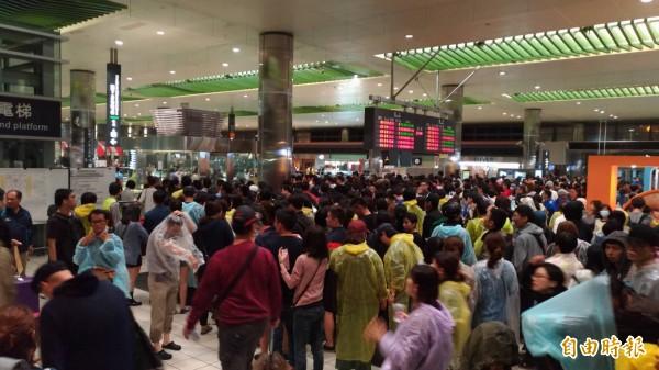 4萬歌迷冒雨挺「酷玩」,高鐵桃園站運量倍增。(記者李容萍攝)