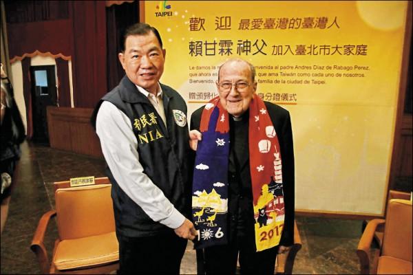 移民署長何榮村(左)致贈國旗圍巾給賴甘霖神父。(記者王冠仁翻攝)