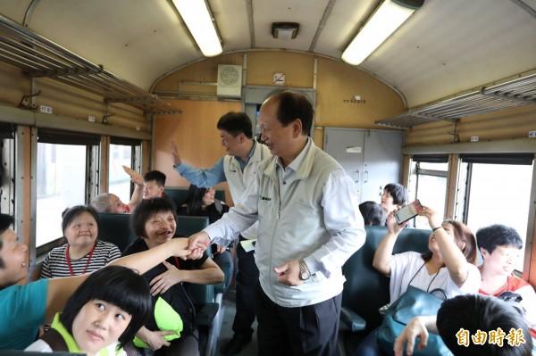 吳澤成與搭乘的民眾握手致意。(記者林敬倫攝)