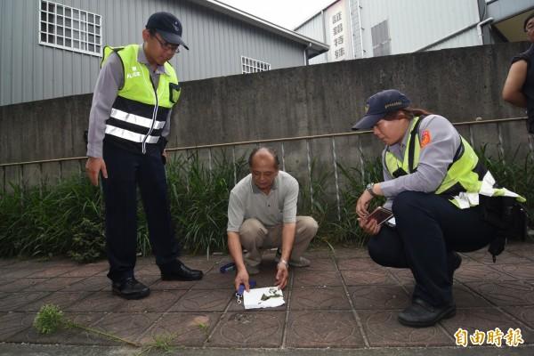 員警與被害人到人行道放置毒餌地點。(記者李忠憲攝)