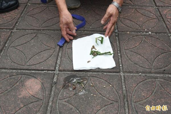 人行道上的毒餌放置地點仍有殘留物。(記者李忠憲攝)