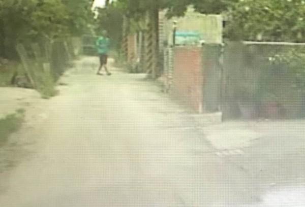 偵防車在小路發現落單的暴力集團王姓成員,王男也發覺被警方盯上,快步走到路旁電線桿。(記者湯世名翻攝)