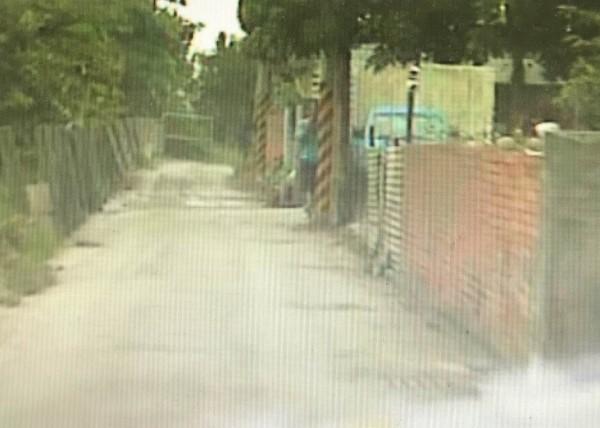 偵防車在小路發現落單的暴力集團王姓成員,王男發覺被警方盯上,快步躲到路旁電線桿。(記者湯世名翻攝)