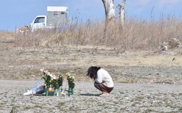 根據福島政府的最新調查,自願離開福島到其他地區生活的民眾,約8成無意回鄉生活。圖為一名女性在上月311地震滿6週年當天,在福島向罹難者致意。(法新社)