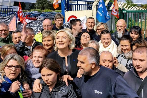 法國總統大選決選候選人、極右派民族陣線領袖瑪琳.勒班(圖中),廿六日到北部亞眠市聲援抗議關廠勞工,受到勞工熱烈歡迎,民眾也搶著跟她合照。(法新社)