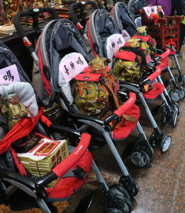 秀水鄉聖靈宮五府王爺、太子爺共6個神尊都坐在嬰兒車內準備遶境,引起轟動。(記者湯世名翻攝)