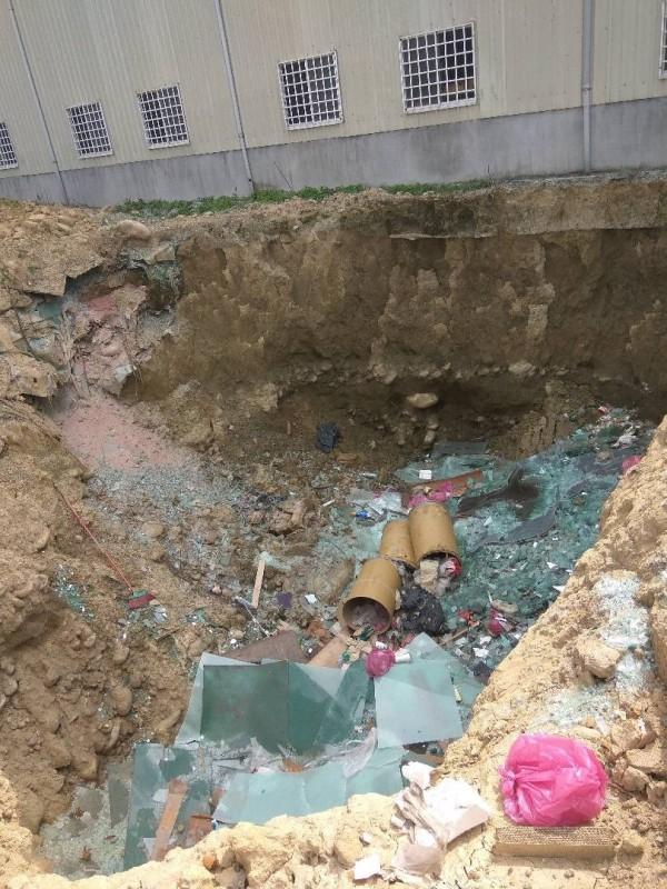 業者在自家廠區內開挖出10公尺大洞,直接掩埋廢玻璃,以省下處理費。(環保局提供)