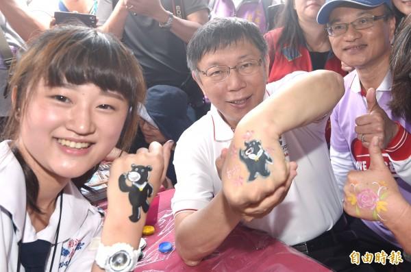 台北市長柯文哲(中)7日出席第五屆愛天使樂活園遊會,參觀攤位時,讓學生在手背上彩繪世大運吉祥物「熊讚」的圖樣。(記者廖振輝攝)