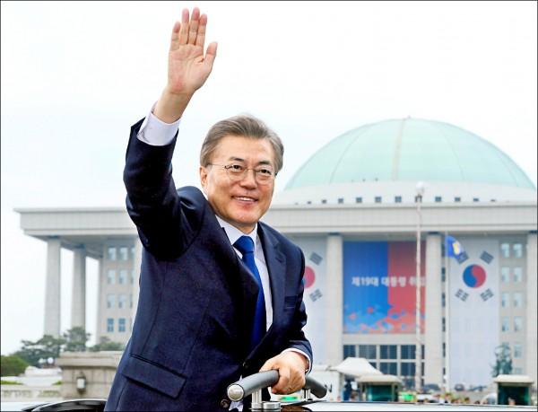 南韓新任總統文在寅十日就職後,搭車從國會大樓離開時,揮手向民眾致意。(路透)