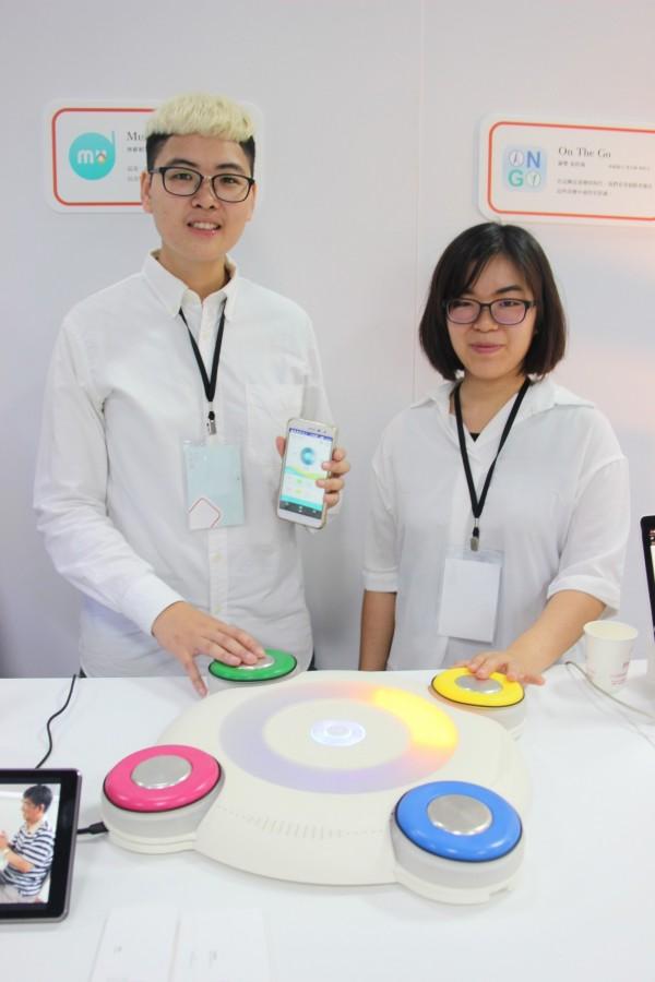 台科大設計系林維娟(右)、戴琳(左)走訪日照中心接觸失智症患者,設計出音樂復健器材「樂活光音」。(台科大提供)