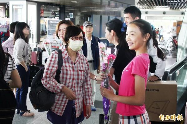 崇文國小學生在高鐵嘉義站送花給女性遊客。(記者林宜樟攝)