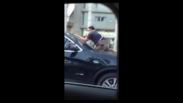 男子趴在行駛中的轎車引擎蓋上。(圖記者張聰秋翻攝)