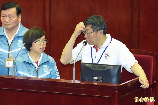 參觀世大運賽事的服裝、旗幟成為議員質詢焦點,讓柯文哲難以回應,和秘書長蘇麗瓊(左)在台上面面相覷。(記者廖振輝攝)