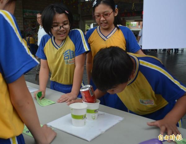 霧峰吉峰國小今天舉辦「全民科學日」,小朋友努力吹氣將鋁罐從紙杯吹出。(記者陳建志攝)