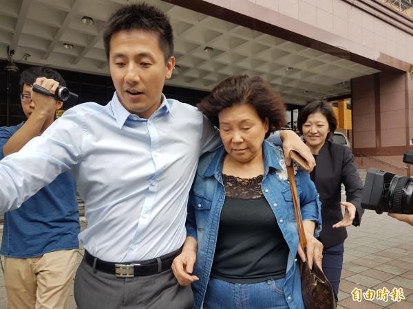 今天下午2點45分,伍蔣清明(左3,穿藍色牛仔衣)覓保4小時30分後辦保離開,面對記者追問是否是清白的?有沒有炒股?她未發一語。(記者錢利忠攝)