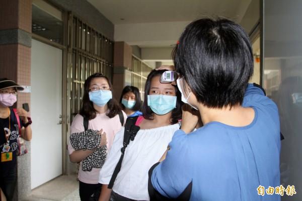 國立宜蘭高商傳出爆發A型流感疫情,圖為今天提前結束畢旅的學生接受校方量體溫。(記者林敬倫攝)