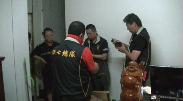 保七警員正在查閱偽酒標籤。(記者楊政郡翻攝)