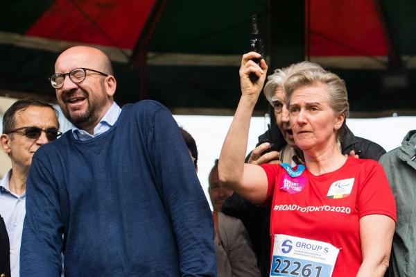 比利時阿斯特里德公主為馬拉松起跑鳴槍,站在一旁的米歇爾皺起眉頭往邊閃。(法新社)
