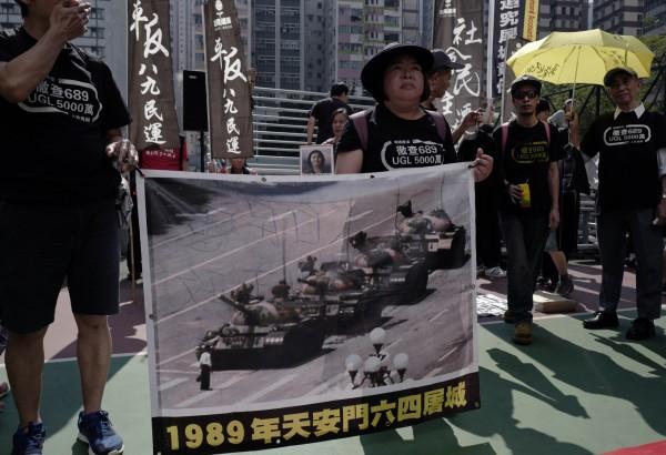 中國微博在六四期間,禁止海外用戶發布影片與照片。圖為香港民眾在今年5月28日紀念六四28週年時,手持天安門坦克人的照片。(美聯社)
