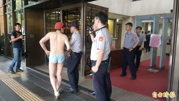 今天下午3點多,1名僅穿內褲的中年男子,手提著1袋衣物,打赤膊到台北地檢署大門外,嘴裡囔囔著喊要提告。(記者錢利忠攝)