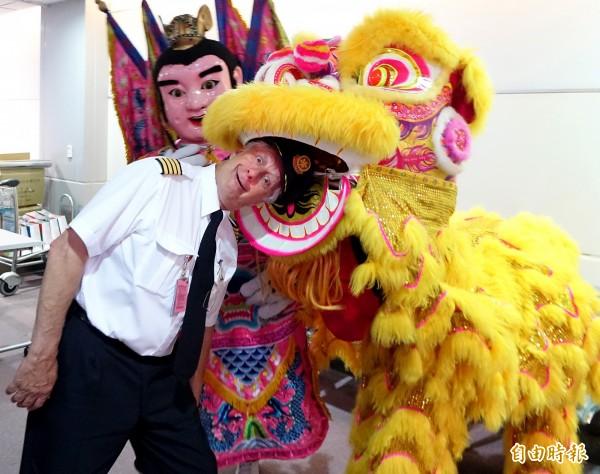 加拿大航空台北-溫哥華直飛航班9日正式啟航,電音三太子及舞獅在登機門口歡迎首航班來台旅客,剛下飛機的機師搞笑的與台味十足的電音三太子及舞獅合影。(記者朱沛雄攝)
