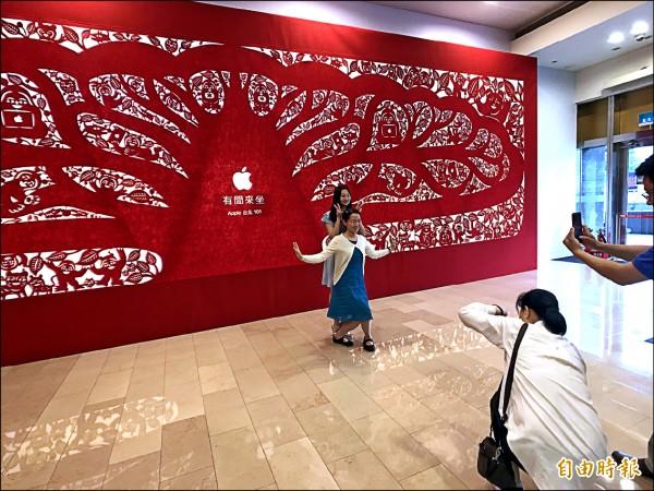 ▲不少民眾趁Apple台北101直營店尚未開幕前到此一遊,和巨幅剪紙作品合影。(記者陳炳宏攝)