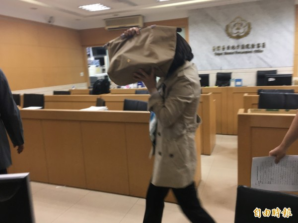 永豐餘前董事長邱秀瑩250萬元交保後,手舉名牌包遮臉。(記者張文川攝)