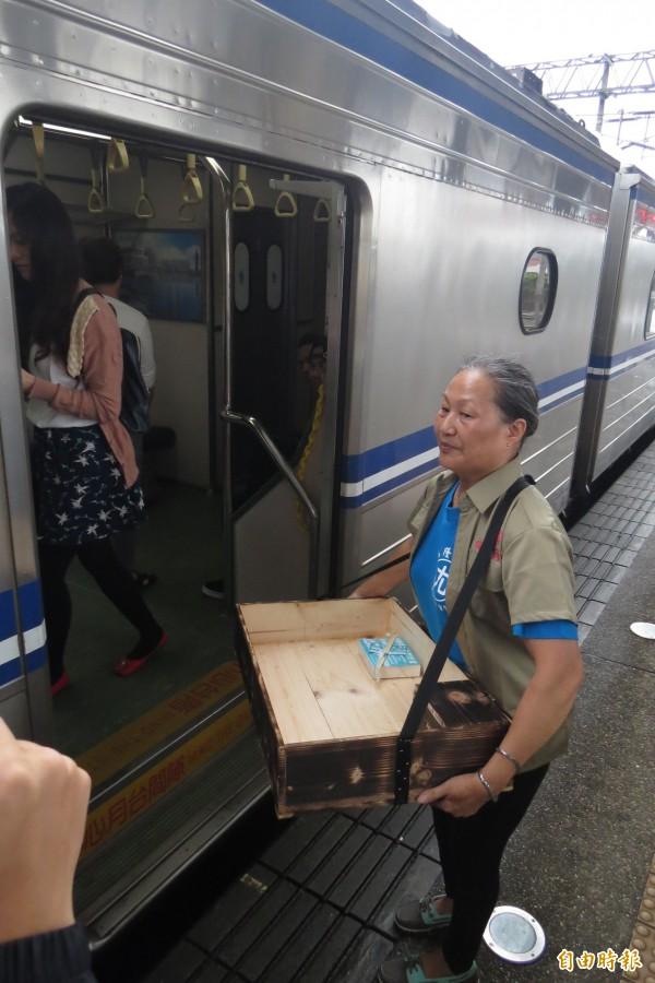 75歲的黃博武,隔了50幾年重新背上便當箱,在月台叫賣回味古早的福隆月台便當,火車上的乘客看到有賣便當,半信半疑跑出來買。(記者俞肇福攝)