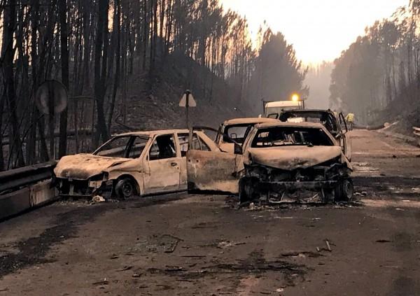 葡萄牙森林大火,在公路逃離不及的汽車被燒毀。(路透)
