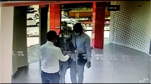 銀行行員迅速將大門上鎖,讓搶匪不得其門而入。