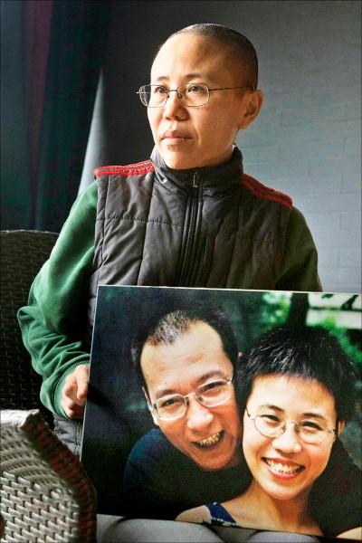 中國諾貝爾和平獎得主劉曉波之妻劉霞,二○一二年十二月在北京自宅手持與丈夫的合照受訪。(美聯社檔案照)
