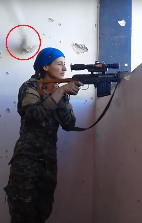 庫德族女戰士差點被伊斯蘭國武裝分子爆頭,敵方的子彈打中後方牆壁。(圖擷自YouTube)