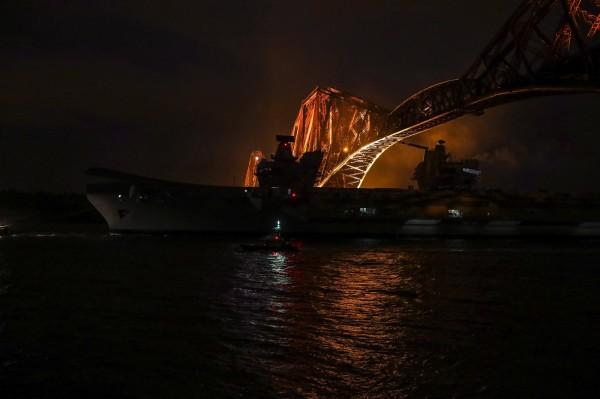 英國最新航母日前下水試航,趁潮位低時通過一座橋。(歐新社)
