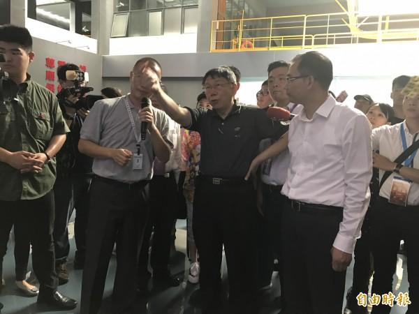 柯文哲稍早露點參訪上海崇明島中華鱘保育成果;特別是,圖左綠色衣服人士為中共維安人員,可見「禮遇」層級提升。(記者郭安家攝)