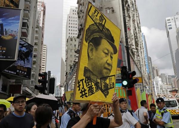 香港「七一遊行」餘6萬市民上街抗議,許多民眾高舉反習近平標語示威。(美聯社)