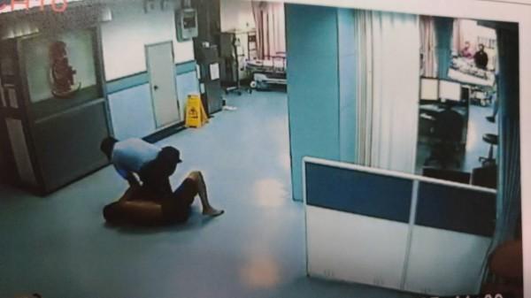 打赤膊的周姓男子被醫院急診室保全人員制伏在地。(記者廖淑玲翻攝)