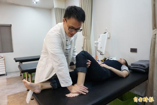 中醫師劉學融以傷科手法把關節錯位高起足壓回扳正。(記者蔡淑媛攝)