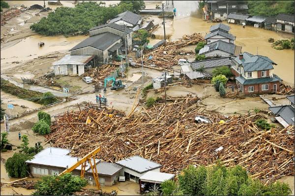 福岡縣朝倉市靠近筑後川附近的住家差點被大量的漂流木淹沒。(法新社)