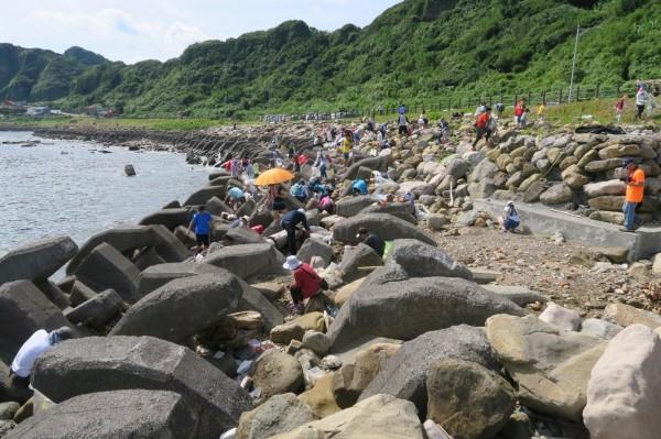 184位的大朋友小朋友,今天(9日)上午不懼艷陽高照,在沙灘上、消波塊中,撿拾人類所製造的垃圾。(圖由陳信助提供)