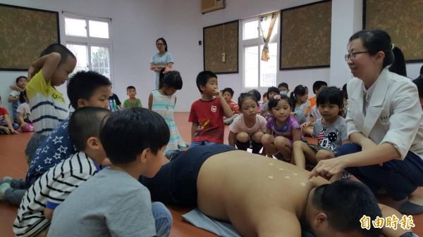 高欣華以慈濟學校的男同學進行穴位示範,小朋友專心聽講。(記者陳賢義攝)